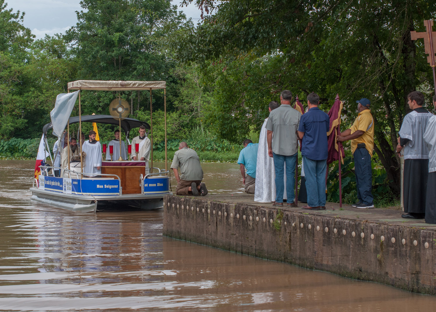 A priest, members of the Knights of Columbus and lay Catholics greet an arriving boat with altar servers during the Aug. 15, 2017, Fete-Dieu du Teche procession in Arnoldville, La. The Lafayette Diocese will hold its annual 38-mile eucharistic boat procession Aug. 15, 2019, celebrating the feast of the Assumption and 254th anniversary of arrival of French-Canadian immigrants who brought the Catholic faith to Acadiana.