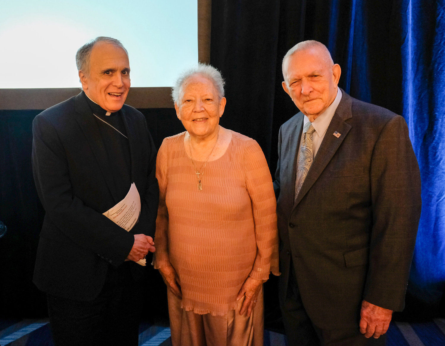 Cardinal Daniel N. DiNardo of Galveston-Houston poses with Gene Kranz, right, former flight director for Apollo 11, and his wife, Marta, during the 2019 Archdiocese of Galveston-Houston Prayer Breakfast in Houston July 30. Gene Kranz, who served as the event's speaker, is a parishioner at Shrine of the True Cross Catholic Church in Dickinson, Texas, near Houston.