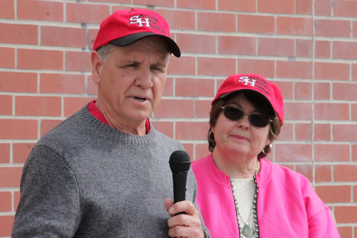 Sacred Heart parishioners Steve and Karen Ellebracht address students, staff and friends of Sacred Heart School when ground was broken for a steel canopy that holds solar panels for the school. The couple made a large contribution toward the project.