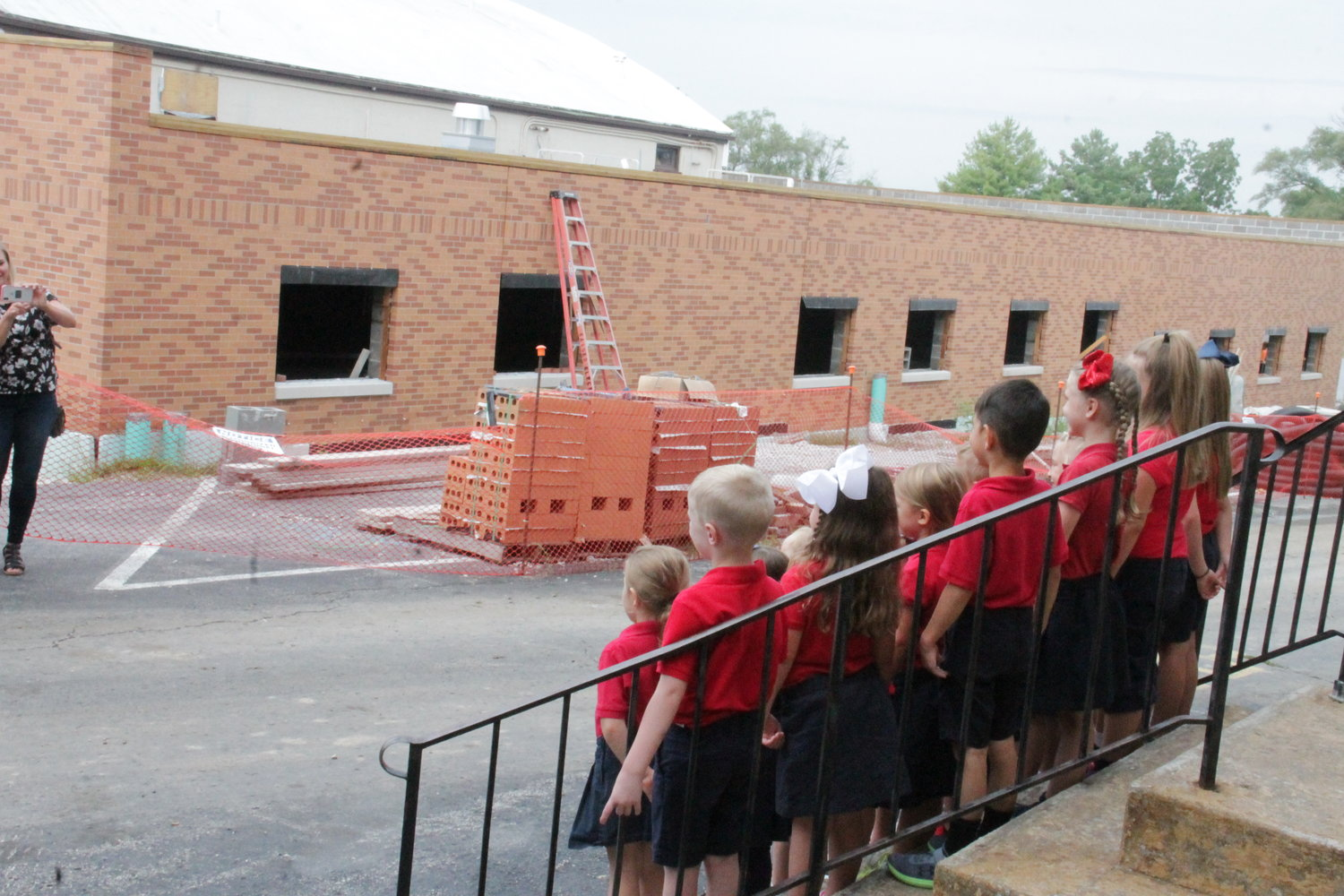 The class of 18 kindergarteners gather for a photo on the steps of St. Joseph Church in Salisbury on their first day of school, while work progresses on a long-awaited addition to St. Joseph School. A parishioner who loved children left her estate to the parish so the addition could be built.
