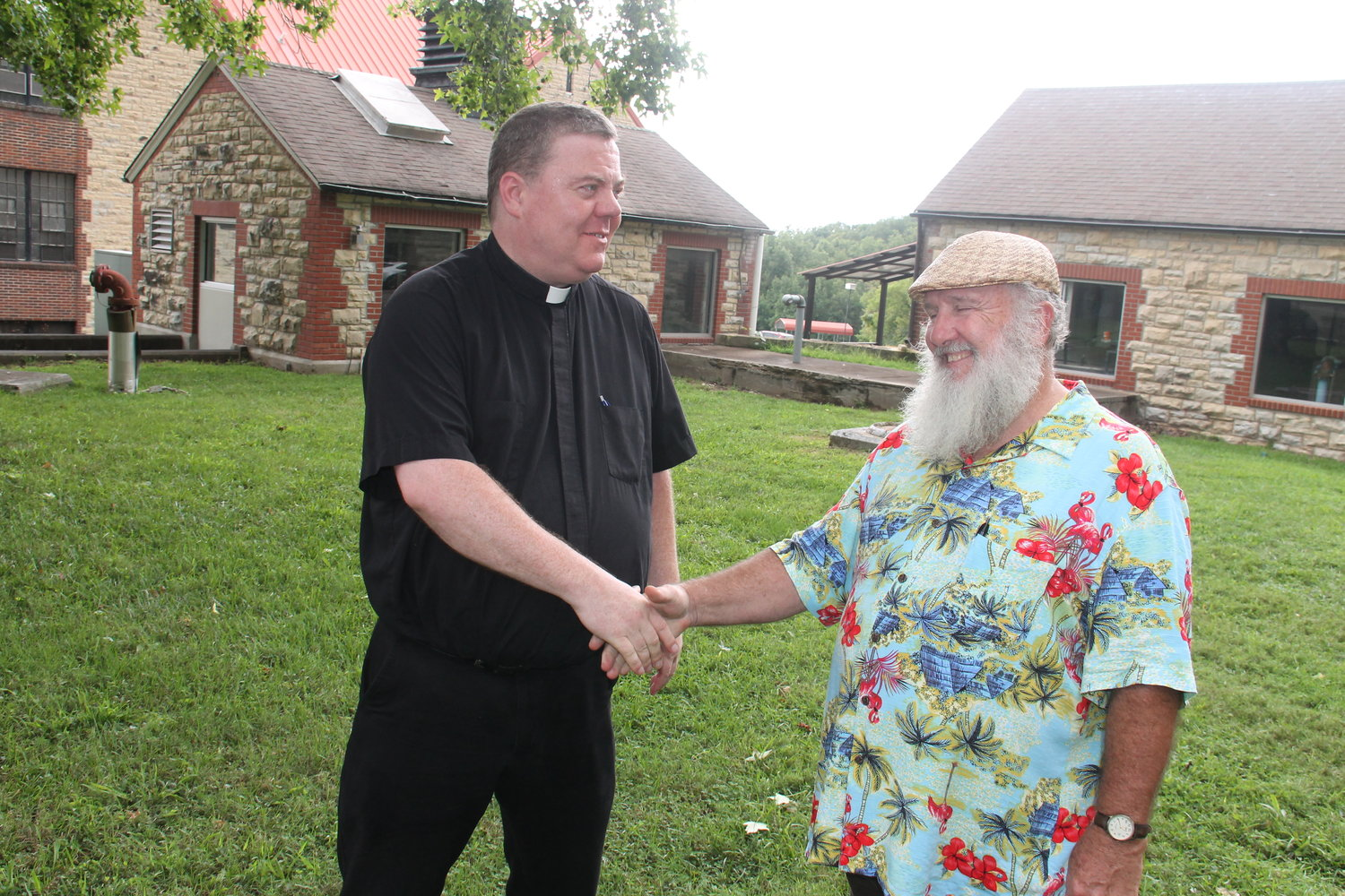Father Joseph Corel, vicar for prison ministry and pastor of the parishes in Pettis County, and Chaplain Jeff Anderson of the Algoa Correctional Center in Jefferson City shake hands after the Adrian Group appreciation barbecue outside ACC.