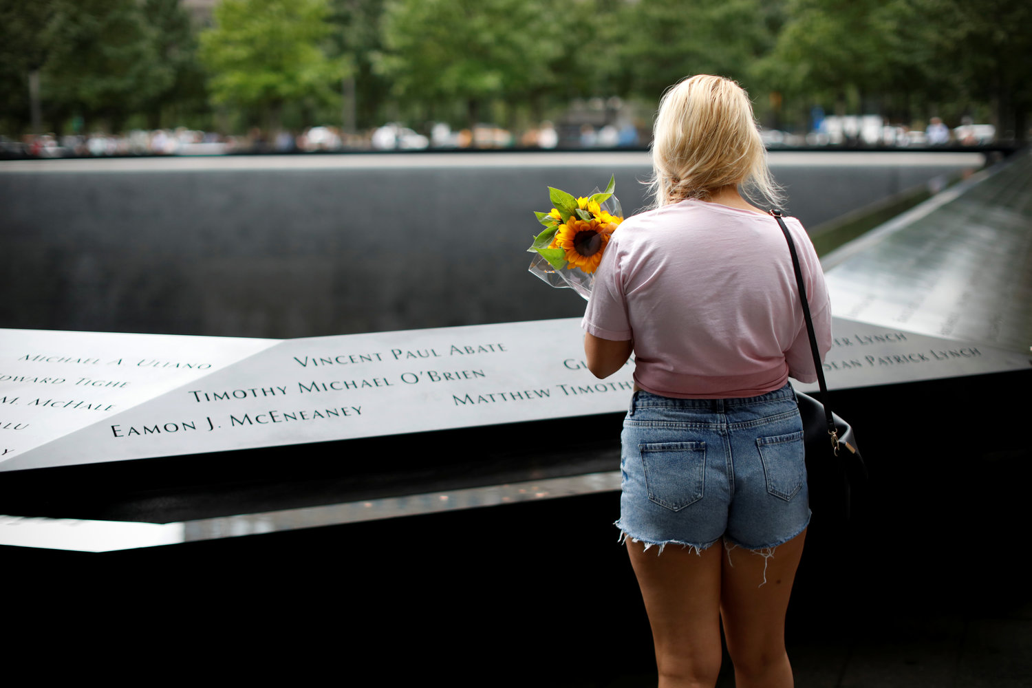 A woman holds a bouquet of flowers as she pauses at the edge of the north reflecting pool at the 9/11 Memorial and Museum in New York City Sept. 10, 2019, the eve of the 18th anniversary of the 9/11 terrorist attacks. Msgr. John Delendick, a longtime New York Fire Department chaplain, still recalls the 9/11 attacks vividly. That first year after the attacks, he said, he doesn't remember how many funerals and memorial Masses he celebrated.