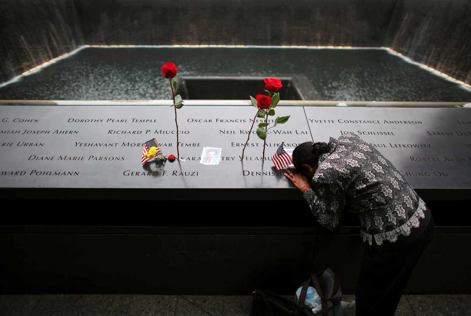 A woman grieves at the inscription of her late husband's name at the national 9/11 Memorial and Museum in New York City Sept. 11, 2014. Msgr. John Delendick, a longtime New York Fire Department chaplain, still recalls the 9/11 attacks vividly. That first year after the attacks, he said, he doesn't remember how many funerals and memorial Masses he celebrated.