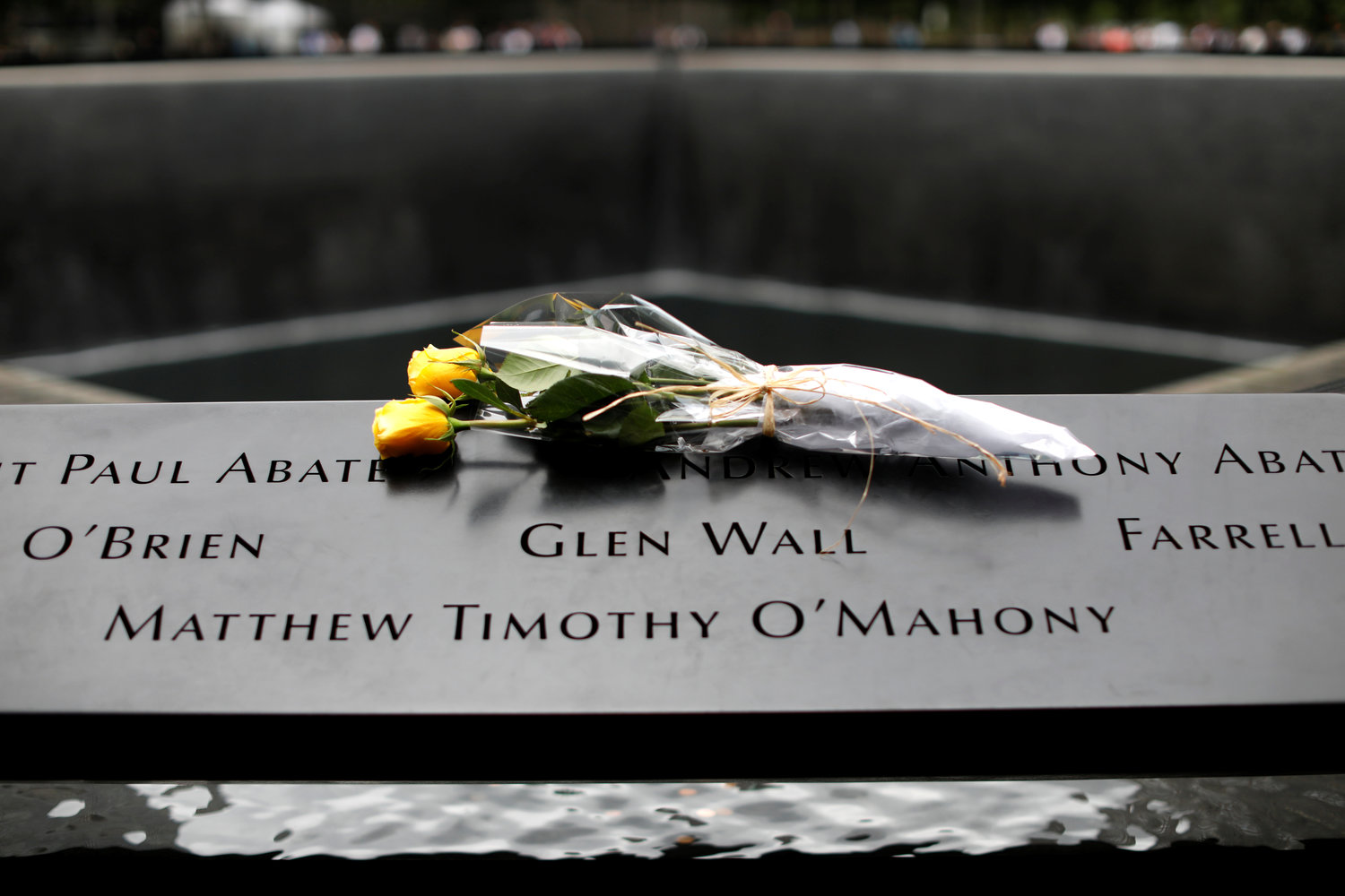 Flowers are seen left at the edge of the north reflecting pool at the 9/11 Memorial and Museum in New York City, Sept. 10, 2019, the eve of the 18th anniversary of the 9/11 terrorist attacks. Msgr. John Delendick, a longtime New York Fire Department chaplain, still recalls the attacks vividly. That first year after the attacks, he said, he doesn't remember how many funerals and memorial Masses he celebrated.
