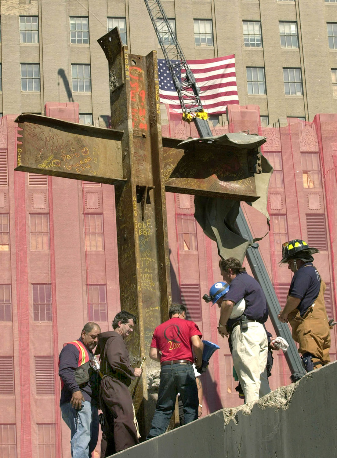 Franciscan Father Brian Jordan, standing with laborers and emergency workers in Oct. 5, 2001, blesses a 17-foot-tall cross formed by steel beams that was recovered from the rubble of the World Trade Center in New York. Msgr. John Delendick, a longtime New York Fire Department chaplain, still recalls the 9/11 terrorist attacks vividly. That first year after the attacks, he said, he doesn't remember how many funerals and memorial Masses he celebrated.