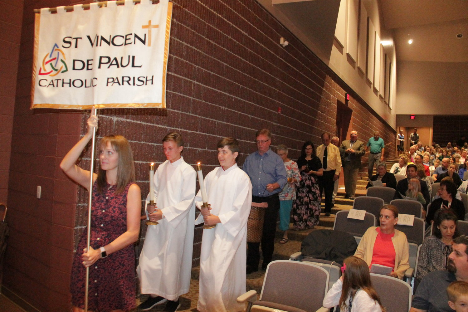 Parishioner Katelin Hladik presents the banner for the parish at the front of the offertory procession.