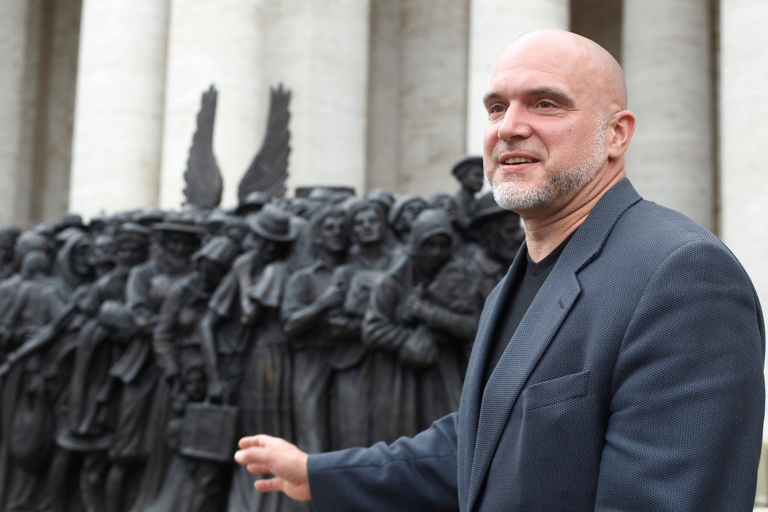 "Sculptor Timothy Schmalz talks about his bronze sculpture, ""Angels Unawares,"" in St. Peter's Square at the Vatican Oct. 1, 2019. Pope Francis attended the unveiling of the statue after a Sept. 29 Mass marking World Day of Migrants and Refugees. (CNS photo/Robert Duncan) See VATICAN-LETTER-MIGRANTS-STATUE Oct. 3, 2019."