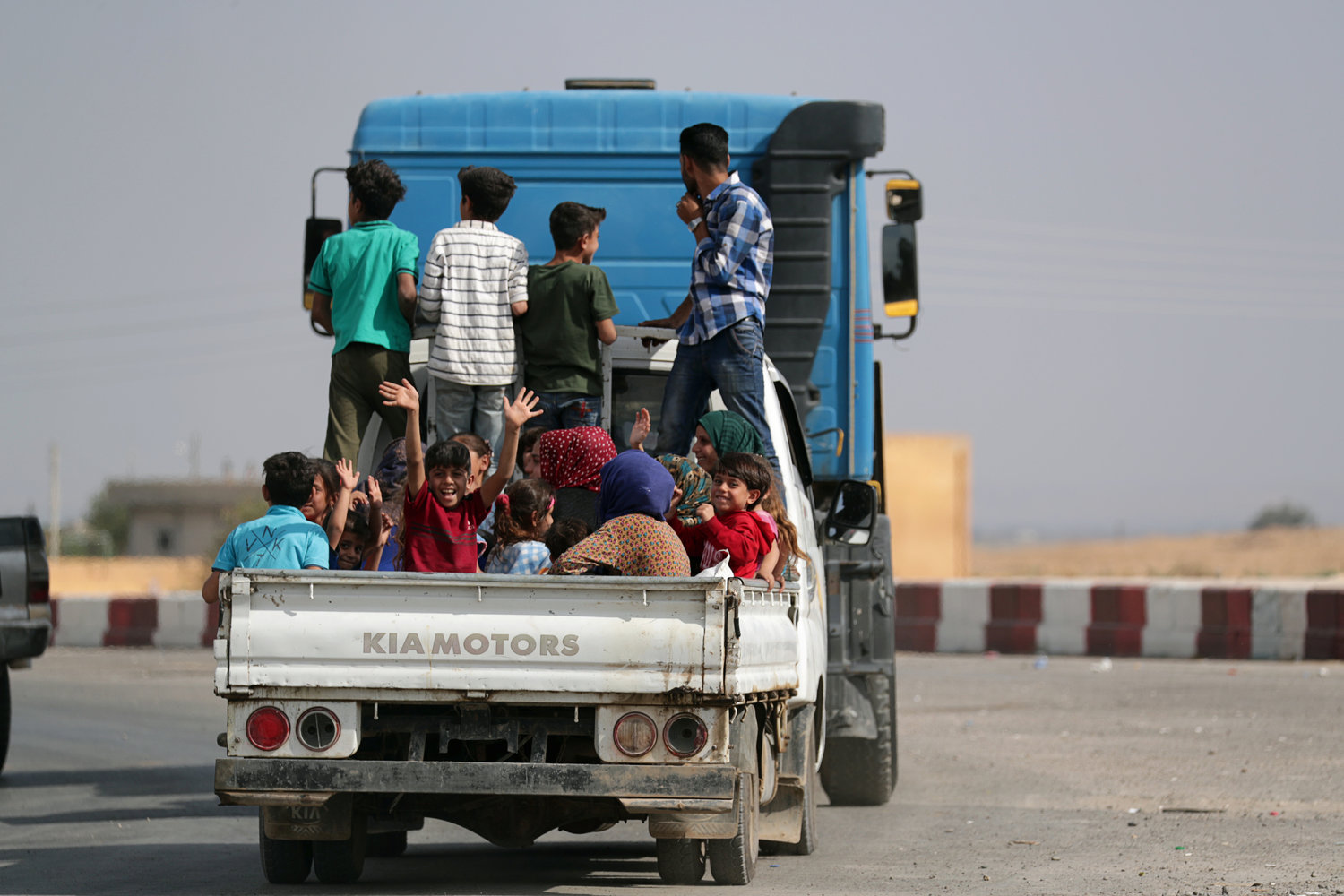 "People ride on the back of a truck in the border town of Tel Abyad, Syria, Oct.14, 2019. During Mass in Rome Oct. 13, Syriac Catholic Patriarch Ignace Joseph III Younan pleaded for ""immediate and lasting peace in northeastern Syria and the preservation of innocent lives, especially for Christians, who are the original and founding component of Syria."""