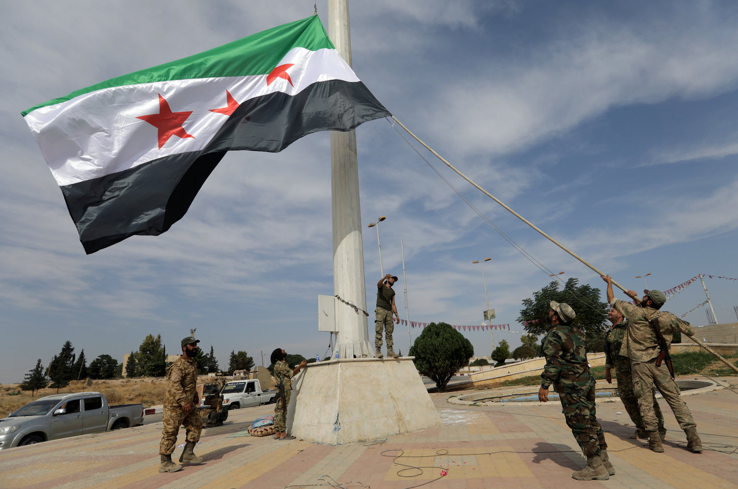 Turkish-backed Syrian rebel fighters raise the Syrian opposition flag at the border town of Tel Abyad, Syria, Oct. 14, 2019.