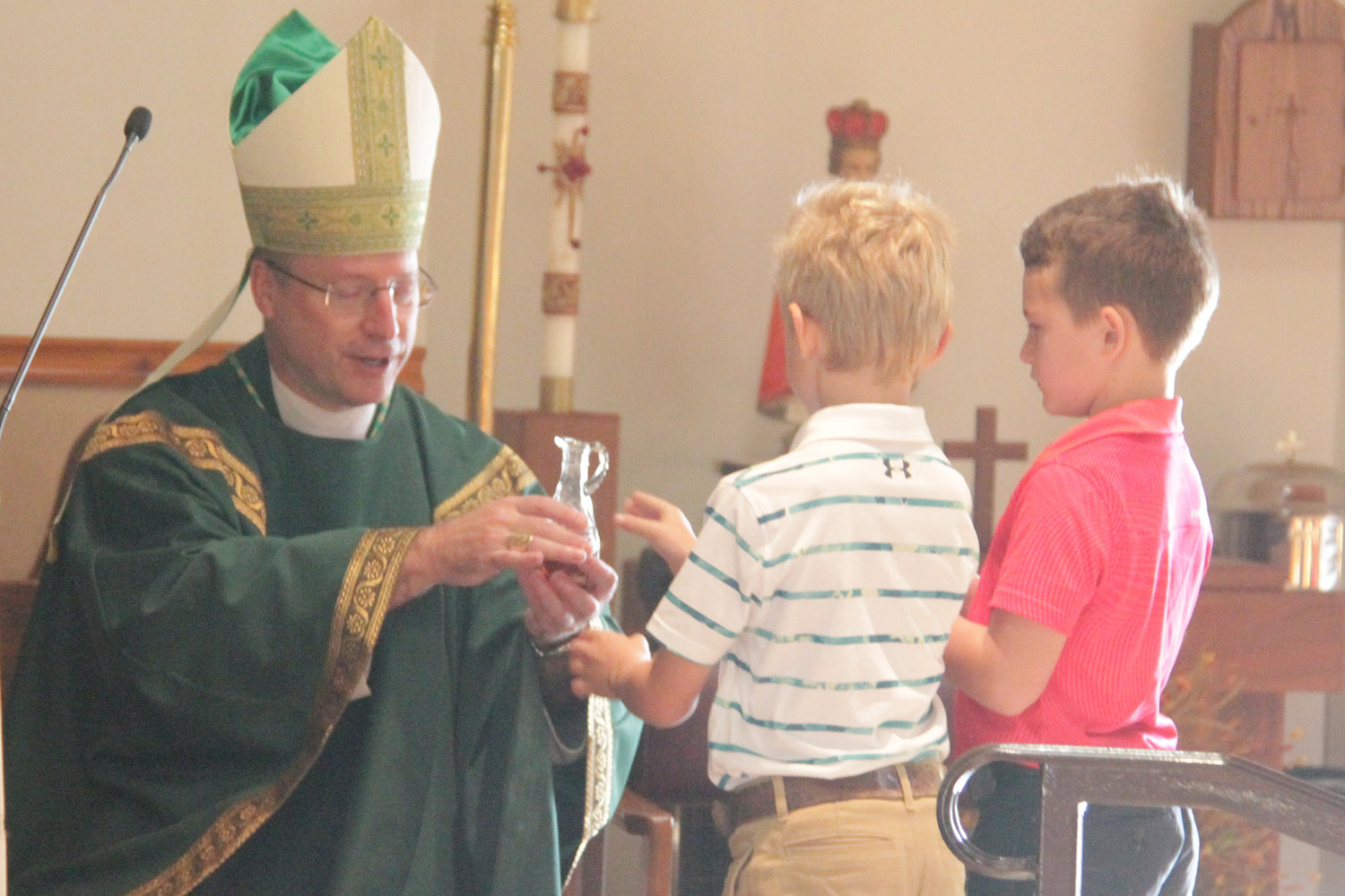 Third-graders at St. Martin School in St. Martins carry out various liturgical roles at an all-school Mass with Bishop W. Shawn McKnight, whom they invited to visit their school.