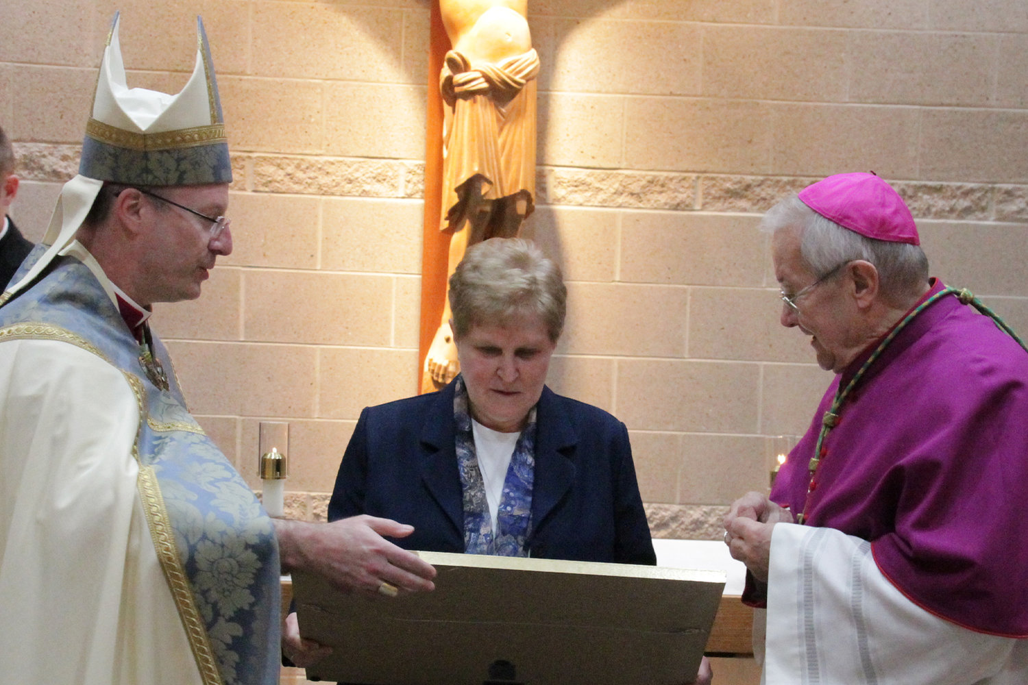Bishop W. Shawn McKnight (left) and Bishop Emeritus John R. Gaydos present Sister Kathleen Wegman SSND the proclamation that came with an award she received from Pope Francis on the occasion of her retirement from full-time ministry.