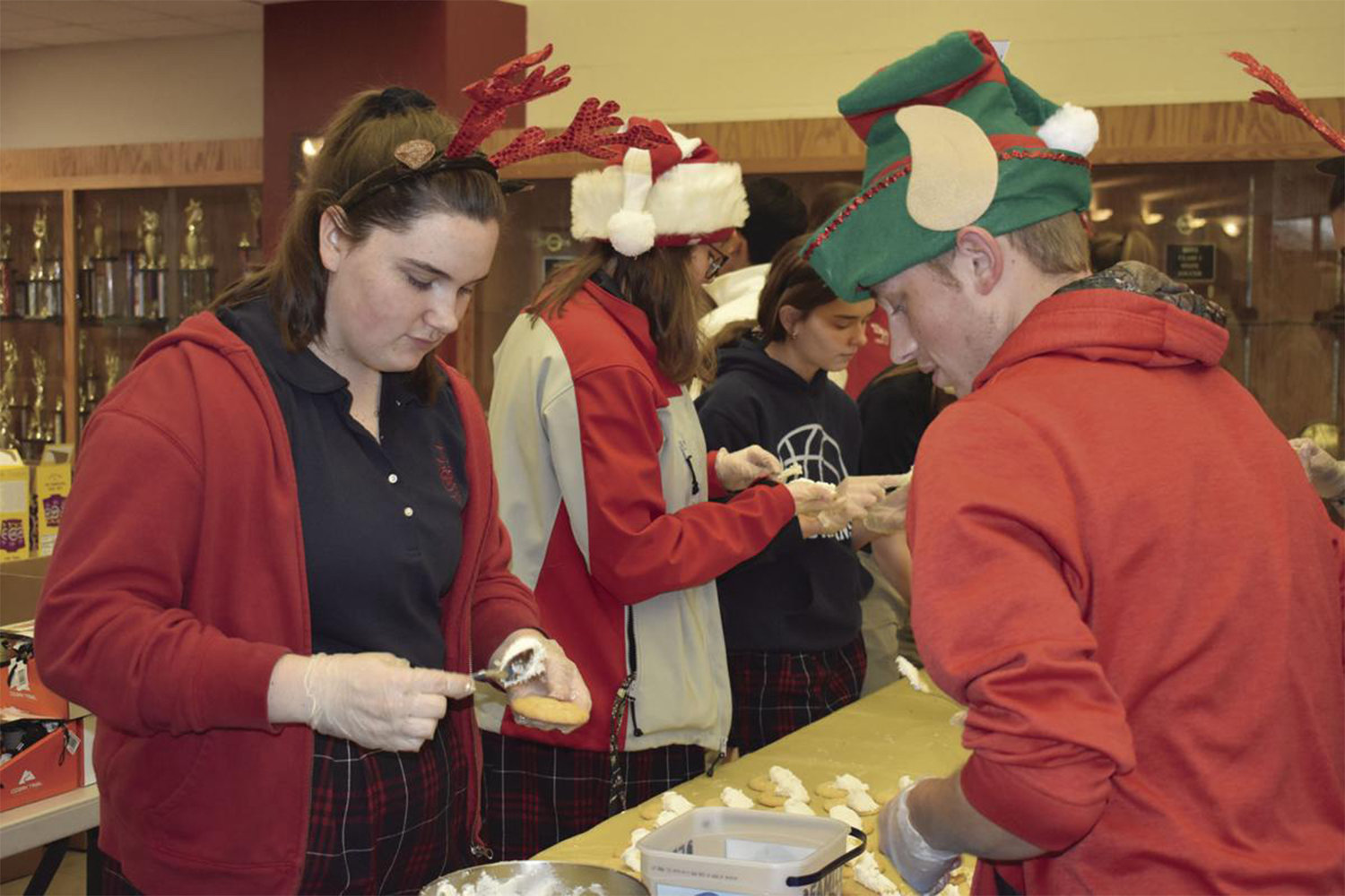 Claire Smeltzer, left, Kelsey Hudson, Caten Lucchesi and Cody Damlo, foreground, help decorate Christmas cookies. They and other members of the SHS Student Council were preparing more than 200 Christmas stockings to be delivered to airmen of the 509th Security Forces at Whiteman Air Force Base in Knob Noster.