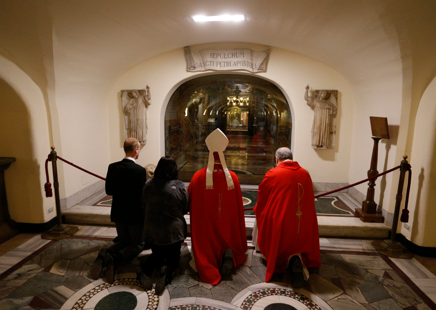 "Bishop W. Shawn McKnight of Jefferson City, Mo., center, prays at the tomb of St. Peter after concelebrating Mass with U.S. bishops from Iowa, Kansas, Missouri and Nebraska in the crypt of St. Peter's Basilica at the Vatican Jan. 16, 2020. The bishops were making their ""ad limina"" visits to the Vatican to report on the status of their dioceses to the pope and Vatican officials."