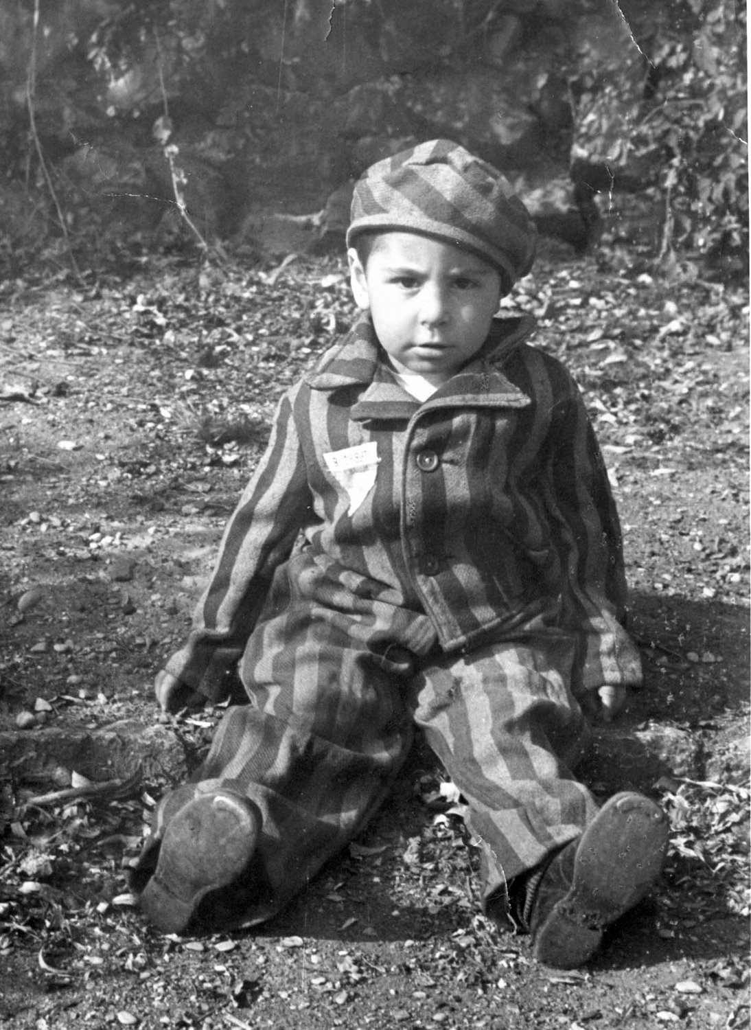 A boy wears a prisoner's uniform after the liberation of the Nazi death camp Auschwitz-Birkenau in 1945 in Oswiecim, Poland. Historians estimate that the Nazis sent at least 1.3 million people to Auschwitz between 1940-45, and it is believed that some 1.1 million of those perished there. Auschwitz was liberated by the Russian Army Jan. 27, 1945.