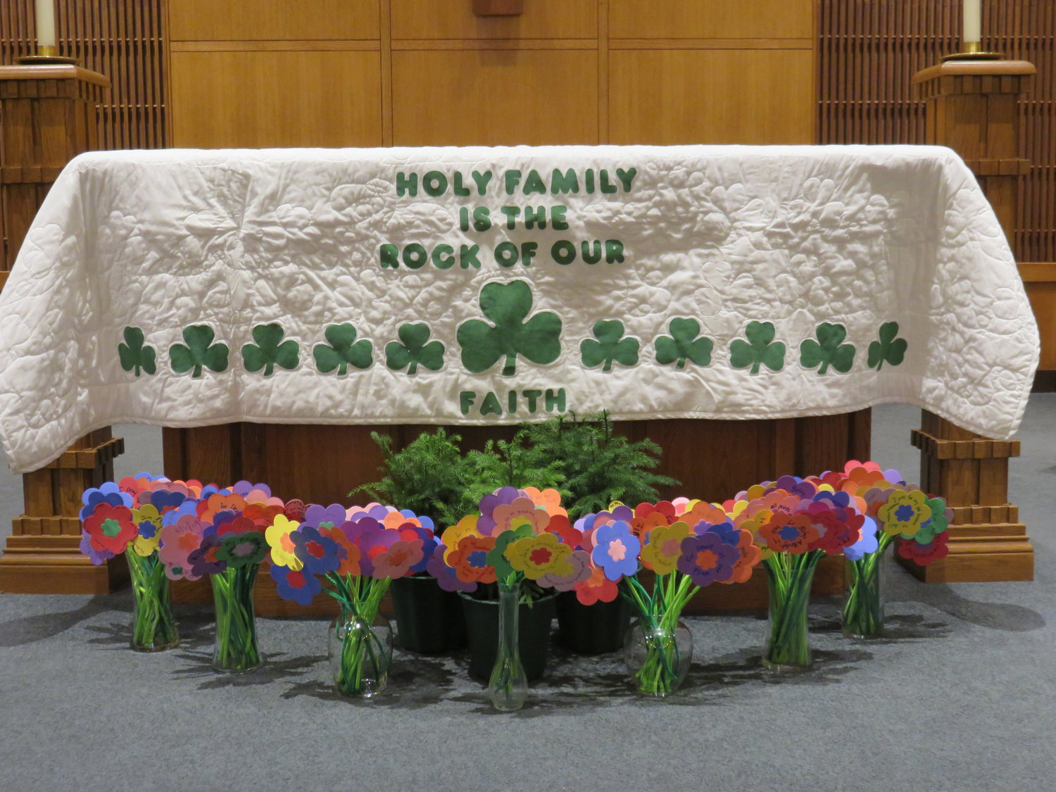 Students' prayer bouquets are displayed in vases before the altar of Holy Family Church in Hannibal during the school's celebration of prayer during Catholic Schools Week.