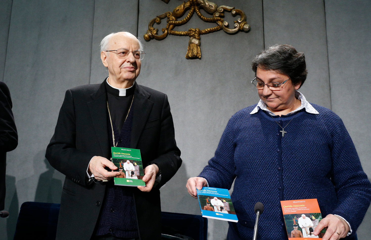 "Cardinal Lorenzo Baldisseri, secretary-general of the Synod of Bishops, and Sister Augusta de Oliveira hold copies of Pope Francis' apostolic exhortation, ""Querida Amazonia"" (Beloved Amazonia), during its release at a news conference at the Vatican Feb. 12, 2020. The document contains the Pope's conclusions from the 2019 Synod of Bishops for the Amazon."