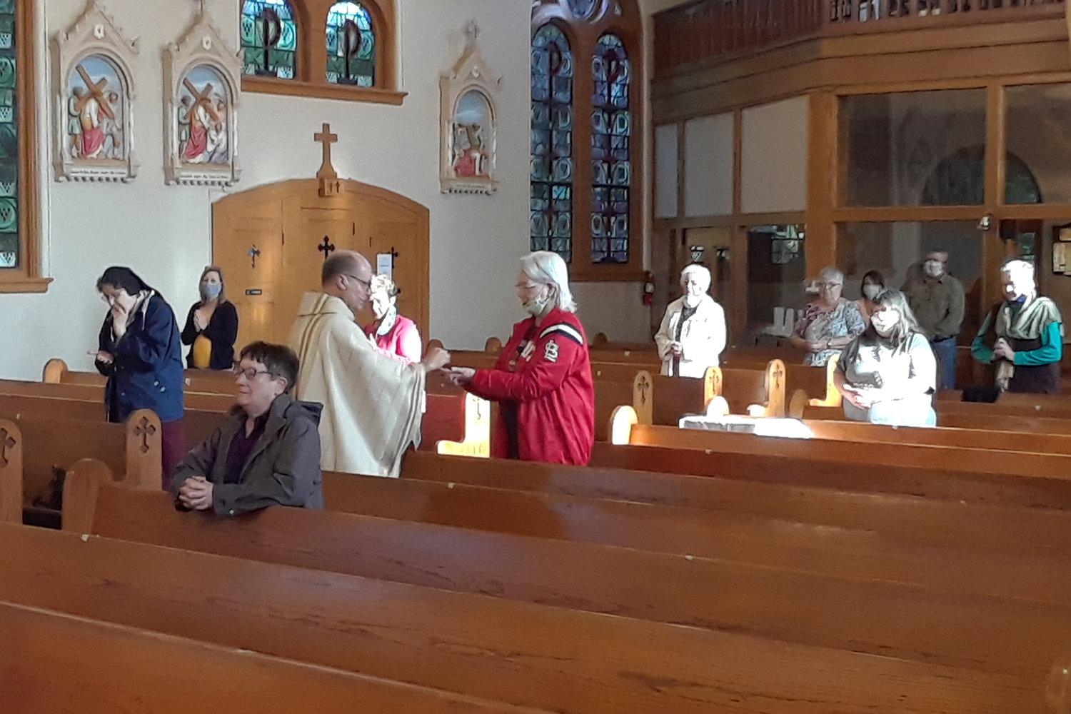 Father William Debo, pastor of Holy Family parish in Freeburg and Sacred Heart parish in Rich Fountain, distributes Holy Communion during Mass on Wednesday, May 6, in Holy Family Church. It was the first publicly celebrated Mass in the Church in seven weeks.