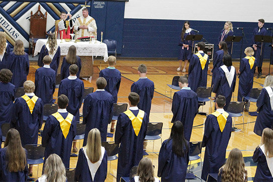 Father Joshua Duncan, a chaplain at Helias Catholic, elevates the Most Precious Blood during the Baccalaureate Mass in the Rackers Fieldhouse.