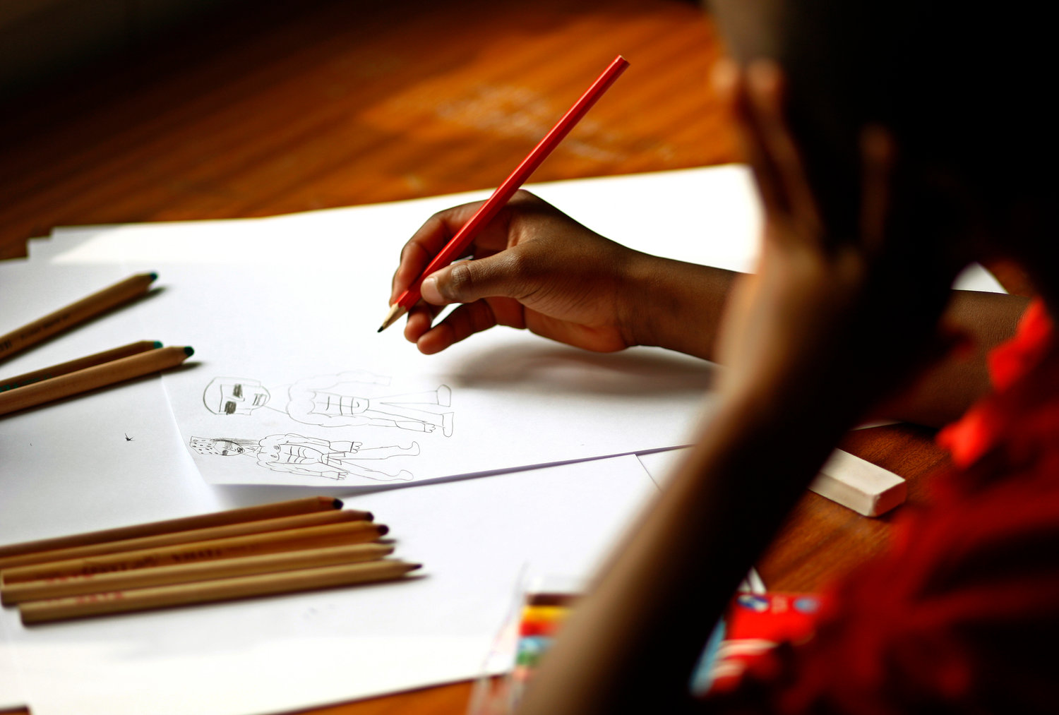 A child is pictured drawing during a therapy session.