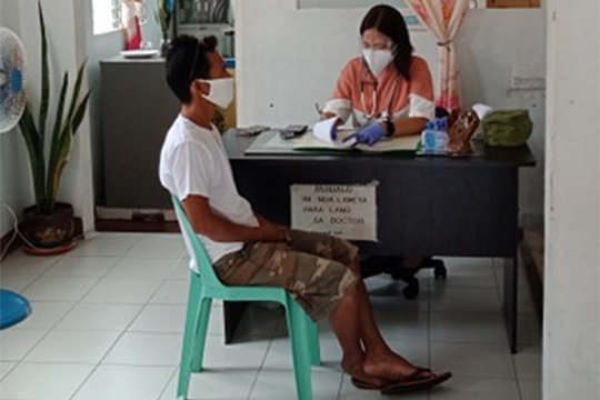 A member of the St. Joseph the Worker Clinic staff collects information from a man seeking treatment.