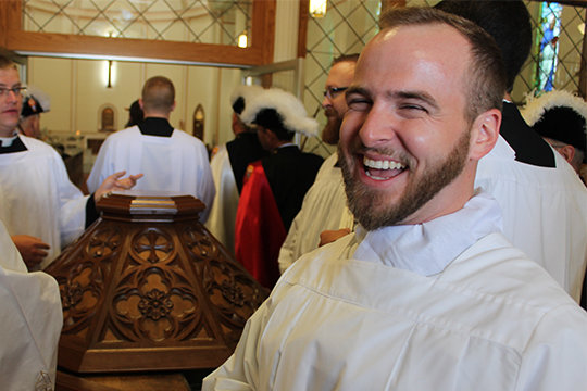 "Father Paul Clark, the diocese's new vocation director, stands next to the baptismal font in St. Joseph Church in Edina, where he was baptized, on the day of his ordination as a transitional deacon in 2017. ""As a community, we stand with the families of those being baptized, to say we desire the fulfillment of this person's vocation, we desire that one day they will join the saints."""