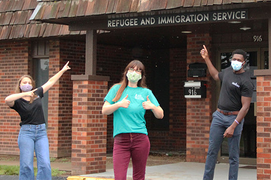Samantha Moog, newly appointed director of Catholic Charities of Central and Northern Missouri's (CCCNM) Refugee Resettlement Services; Grace Wildenhaus, a newly-appointed associate director, and refugee case manager David Mazimano point the way to their Columbia office.