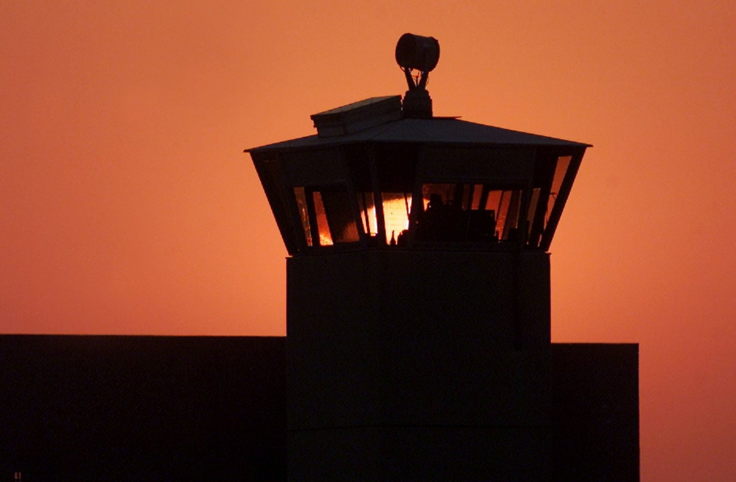 The sun sets behind one of the guard towers at the Federal Correctional Complex in Terre Haute, Ind., June 10, 2001. The death chamber at the correctional facility is where the federal death penalty is carried out.