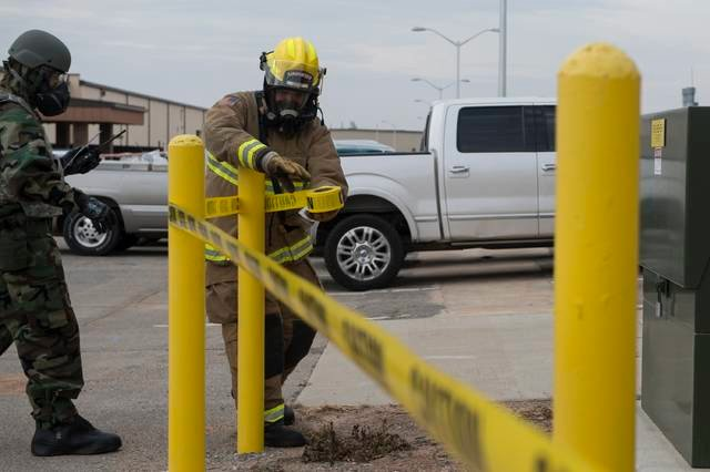 U.S. Air Force Senior Airman Trenton Reddy, a fire protection member assigned to the 97th Civil Engineer Squadron, puts up caution tape, Dec. 6, 2018, at Altus Air Force Base, Okla. During the training exercise, fire protection members had to respond to the situation using wartime procedures like cordoning off hazardous areas.