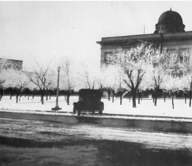 From the Howard Cotner collection, this photo shows the Jackson County Courthouse in 1928 covered in a blanket of snow. Outside the courthouse is an orchard of peach trees. The courthouse looked quite different on Thursday, though still covered in snow.