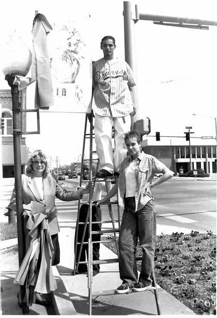 Genaro De Los Santos and Lisa Horton help Kathy Hale and Barbara Behrns hang banners around downtown Altus. Shortgrass and Main Street Altus with Deanna Roberts' art class provide the banners to go around the square in 2000.