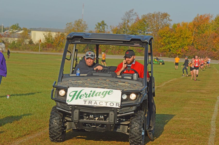 Athletic Director Jason Abner driving a 'gator' with an area coach. They were helping with the annual Clinton Invitational Cross Country Meet. Mr. Abner is leaving the Clinton SD after ten years.