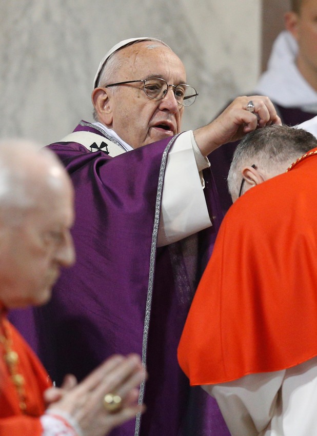Pope Francis places ashes on the head of Cardinal Pietro Parolin, Vatican secretary of state, during Ash Wednesday Mass at the Basilica of Santa Sabina in Rome Feb. 14.