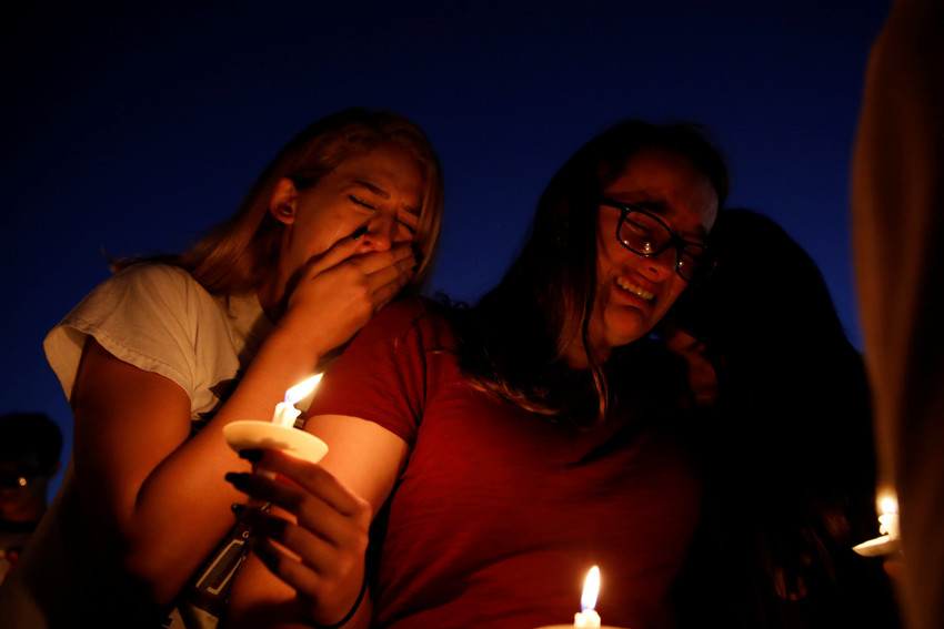Students mourn during a candlelight prayer vigil Feb. 15 for the victims of a mass shooting at nearby Marjory Stoneman Douglas High School in Parkland, Fla. At least 17 people were killed in the Feb. 14 shooting. The suspect, 19-year-old former student Nikolas Cruz, is in custody.
