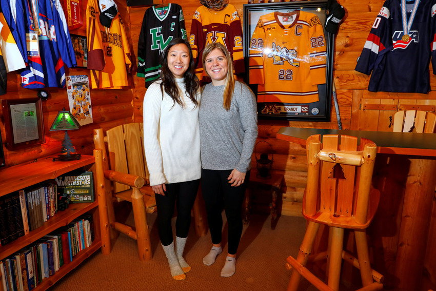 Hannah Brandt poses with her adopted sister Marissa, left, on Christmas day in 2017 at the family home in St. Paul, Minn. The Catholic siblings participated in the 2018 Winter Olympics on separate ice hockey teams. Hannah Brandt played for the U.S. and Marissa Brandt for the combined Koreas.