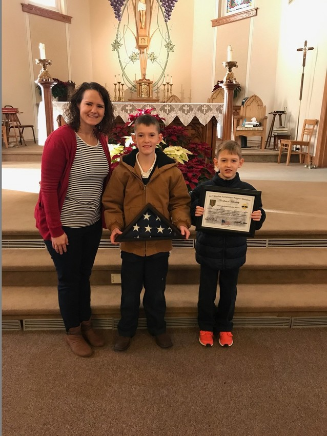 TIPTON: St. Andrew School students Johnathon and Jordan Ehlers present to Principal Abby Martin a U.S. flag and 541st Combat Sustainment Support Battalion (CSSB) certificate of authenticity, stating that the flag had been flown over the 541st CSSB at Camp Buehring in Kuwait in support of Operation Spartan Shield. Johnathon and Jordan are nephews of Sergeant First Class Kris W. Schmidt, who presented the flag to the St. Andrew students and staff for outstanding and generous support of the Missouri National Guard's 548th Transportation Company.