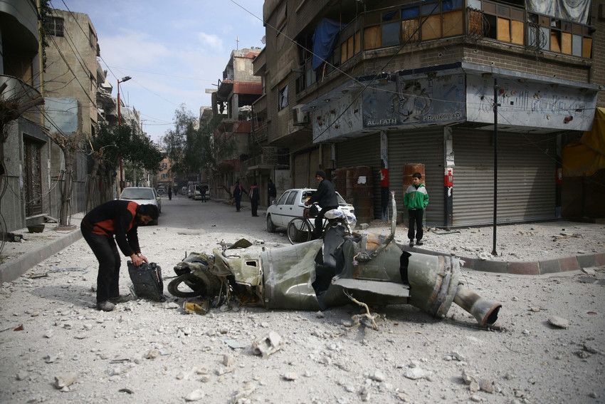 A man inspects the remains of a missile Feb. 23 in the besieged enclave of East Ghouta, near Damascus, Syria.