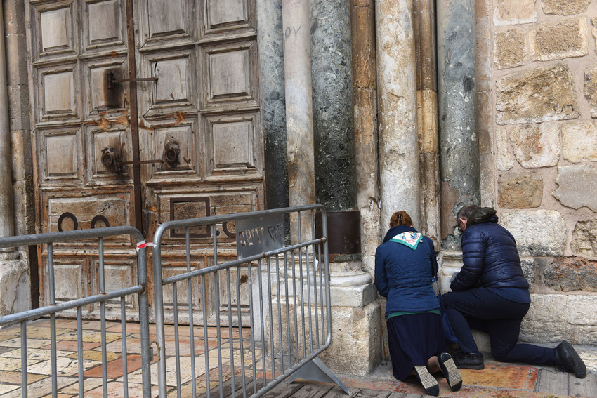 """Tourists pray outside the locked doors of the Church of the Holy Sepulcher Feb. 26 in Jerusalem's Old City. Protesting several recent actions they described as a """"systematic campaign against the churches and the Christian community in the Holy Land,"""" the heads of Christian churches announced Feb. 25 they were closing of the doors of the church."""