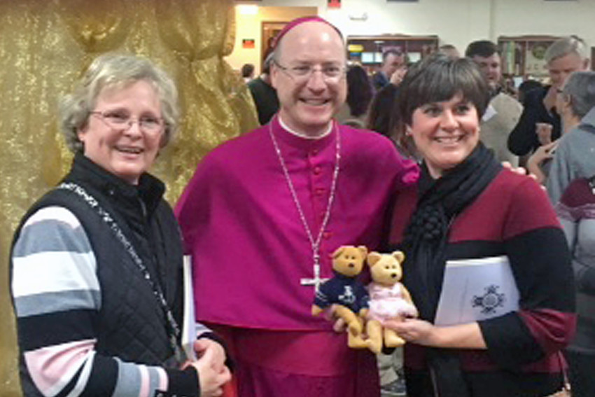 Sedalia's Sacred Heart School kindergarten teachers Jeannine Dove and Rhonda Kusgen and their journal bears, Fuzz and Honey, greet Bishop W. Shawn McKnight at a reception after the Rite of Election and Call to Continuing Conversion on Feb. 18 in the Cathedral of St. Joseph in Jefferson City. Mrs. Kusgen is preparing for initiation into the Catholic Church at the Easter Vigil. Mrs. Dove is her sponsor.