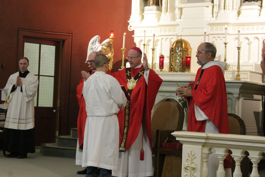 Bishop W. Shawn McKnight, accompanied by Father James Finder of the Argyle and Koeltztown parishes and Father Bill Debo of the Freeburg and Rich Fountain parishes, leads a prayer during the Feb. 28 Confirmation Mass in Sacred Heart Church in Rich Fountain. It was the newly ordained bishop's first Confirmation Mass.