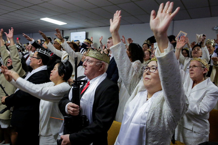 People hold AR-15 rifles at a commitment ceremony at the World Peace and Unification Sanctuary Church in Newfoundland, Pa., Feb. 28. Engaged couples were encouraged to bring the weapons by the sanctuary, which is part of the Unification Church.