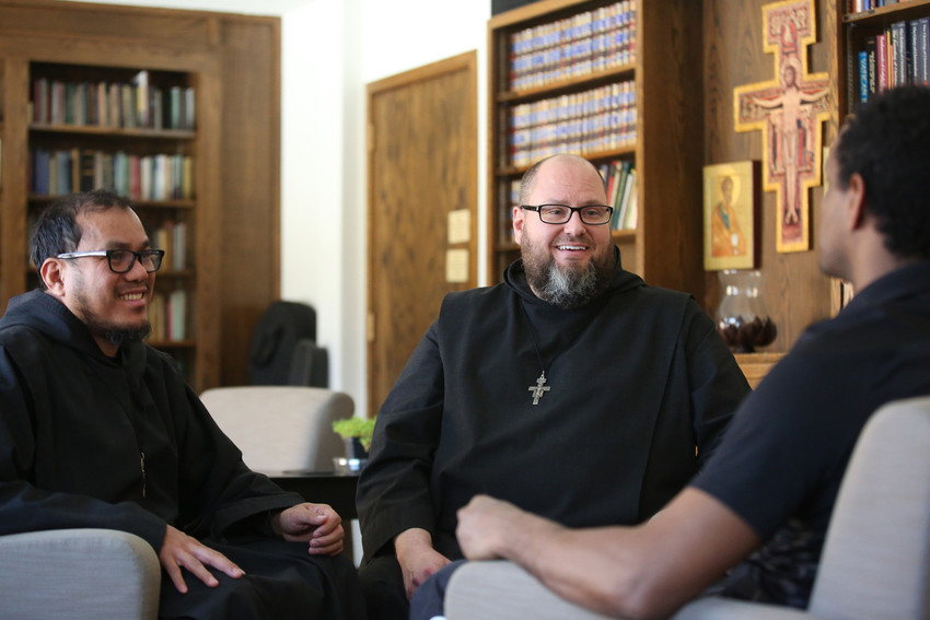 """Franciscan Brothers of Peace Antonio Pagba and Conrad Richardson talk with """"David"""" at the friary in St. Paul, Minn., in this undated photo. The brothers have been helping victims of torture since the mid-1990s."""