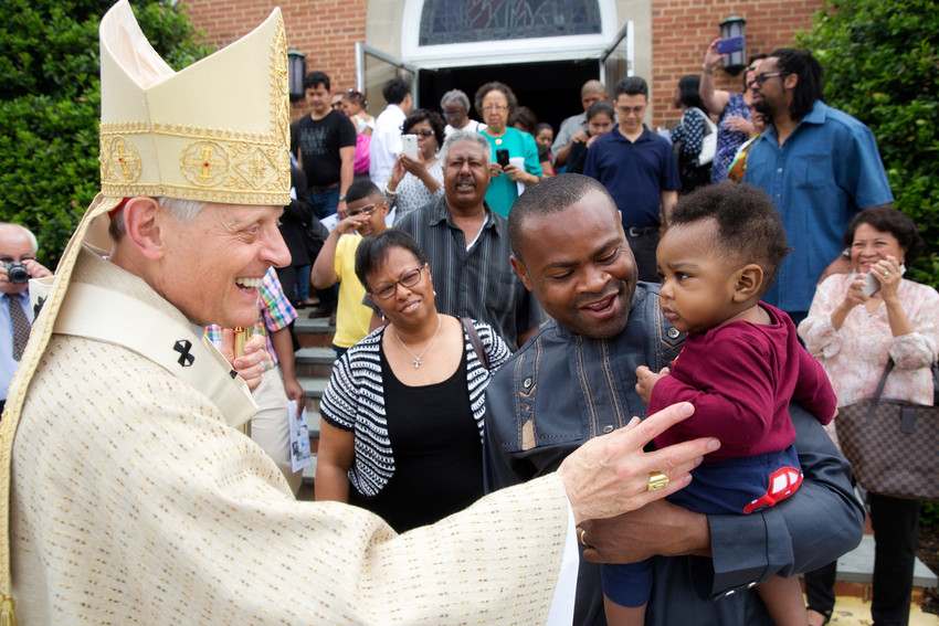In this 2015 file photo, Washington Cardinal Donald W. Wuerl greets parishioners at St. John Baptist de la Salle Parish in Chillum, Md.