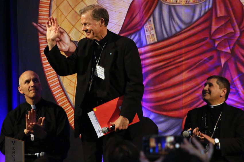 Archbishop John C. Wester of Santa Fe, N.M, waves after being introduced at a bishops' panel Feb. 24 in Phoenix at the V Encuentro gathering for Region 13. At left is Bishop Steven Biegler of Cheyenne, Wyo., and to the right is Auxiliary Bishop Jorge Rodriguez-Pena of Denver.