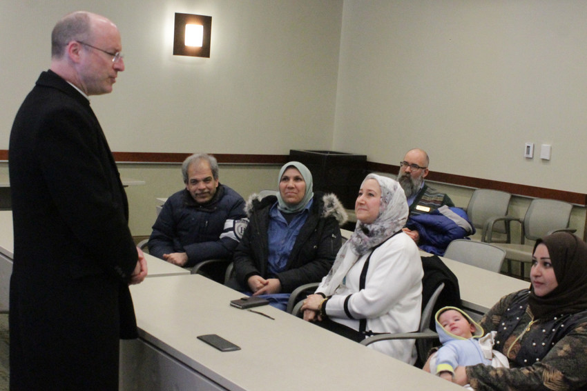 Bishop W. Shawn McKnight visits with families who have recently resettled in the Jefferson City diocese with assistance from Refugee and Immigration Services of Catholic Charities of Central and Northern Missouri.