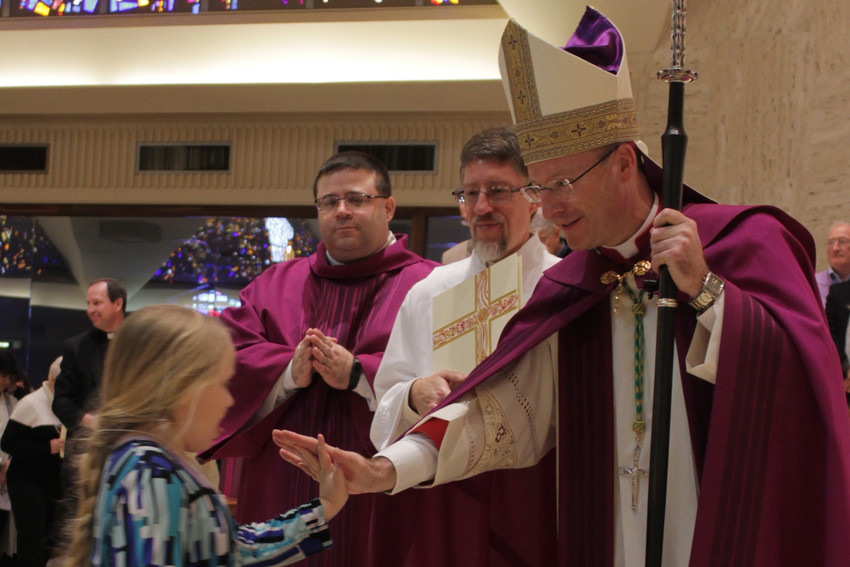Bishop W. Shawn McKnight greets a young catechumen who's seeking baptism in the Catholic Church at Easter, during the Rite of Election and Call to Continuing Conversion on Feb. 18 in the Cathedral of St. Joseph in Jefferson City.