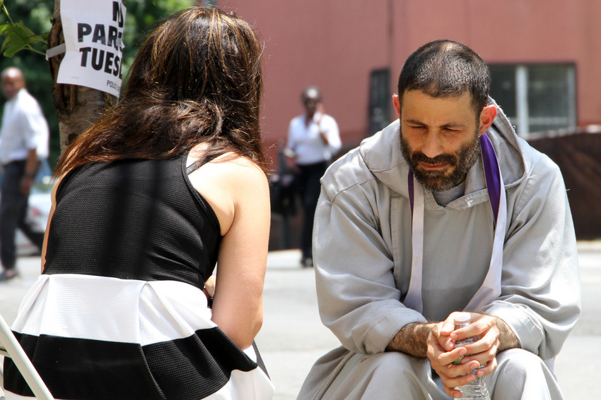 Father Gabriel Bakkar, a member of the Franciscan Friars of the Renewal, listens to a woman's confession during a block party June 13 at St. Crispin Friary in the Bronx borough of New York. The friars were celebrating receiving Vatican recognition as a religious institute of pontifical right. Founded in 1987 in the Archdiocese of New York, the community has 125 members ministering to the poor in the U.S., Honduras, Nicaragua, Ireland and the United Kingdom.