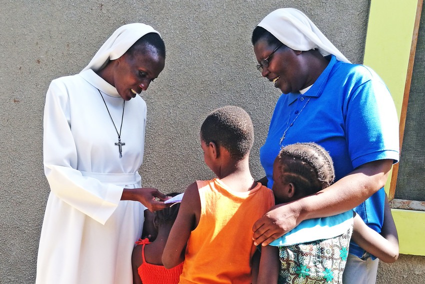 Children at the Pope Francis Rescue Center in Malindi, Kenya, present their homework to Sister Benedicta, a counselor from Sisters of the Holy Family, and Sister Veronica Nyambura.