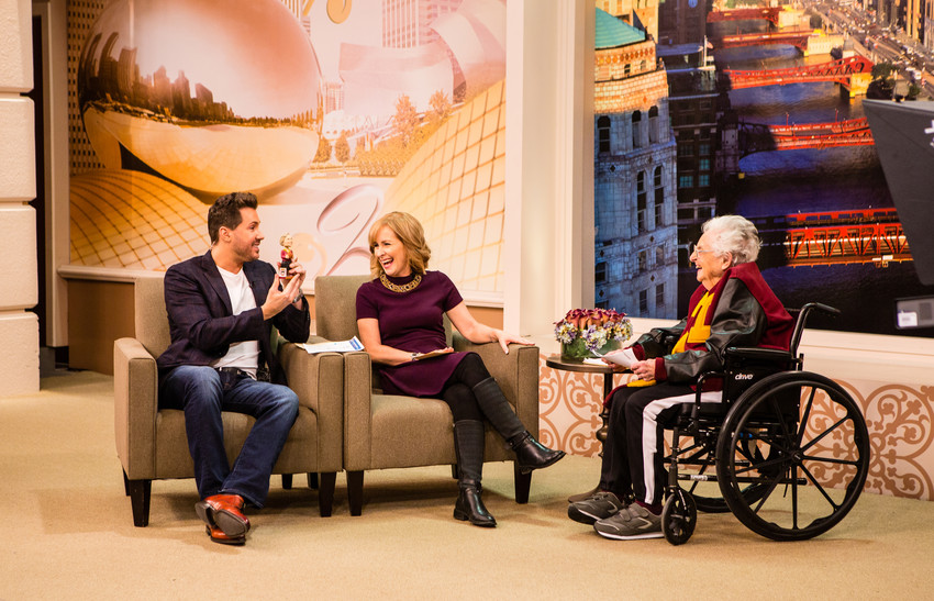 """Sister Jean Dolores Schmidt, 98, longtime chaplain of the Loyola University Chicago men's basketball team and campus icon, right, makes an March 12 appearance on """"Windy City Live"""" with Tracy Butler and co-host Ryan Chiaverini. Sister Jean talked about her bracket and the team's NCCA tournament run. Chiaverini is holding up a bobblehead of Sister Jean. (CNS photo/courtesy Loyola University Chicago) See LOYOLA-CHICAGO-CHAPLAIN March 16, 2018."""