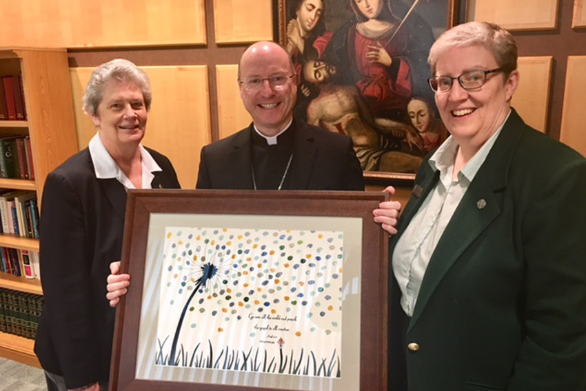Sister Elizabeth Youngs SCL, diocesan superintendent of Catholic schools, and Sister Julie Brandt SSND, associate school superintendent, present to Bishop W. Shawn McKnight an artwork representing pledges of prayer and acts of love and sacrifice from Catholic school students, faculty and staff.