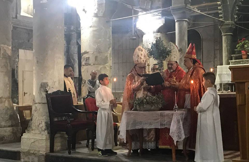 Syriac Catholic Patriarch Ignace Joseph III Younan concelebrates Palm Sunday Mass March 25 at the Cathedral of the Immaculate Conception in Qaraqosh, Iraq. At left the pillars show damage from Islamic State militants.